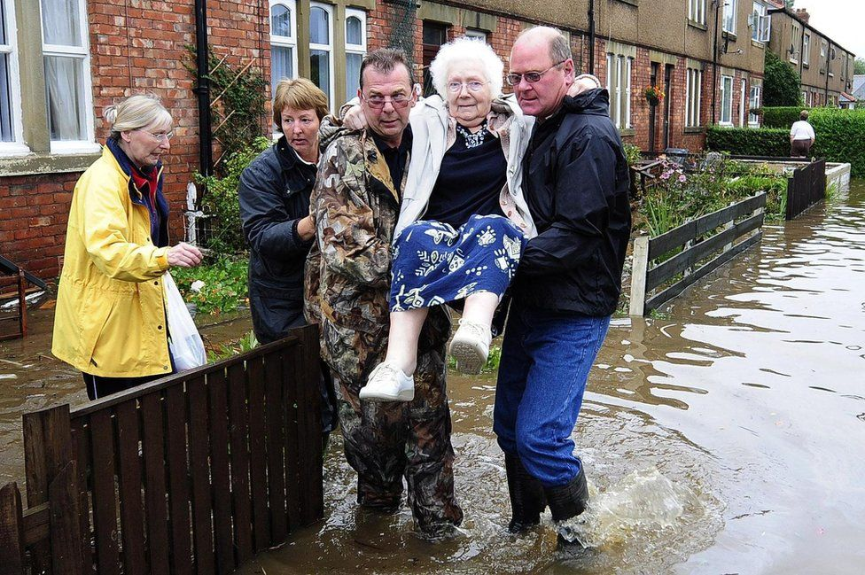 An elderly resident is carried to safety from a flooded street
