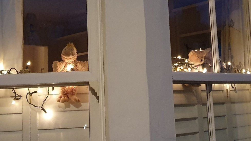 Teddy bears lit up in a window in London
