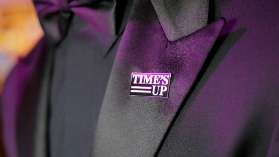 Joe Jonas wearing a Time's Up pin
