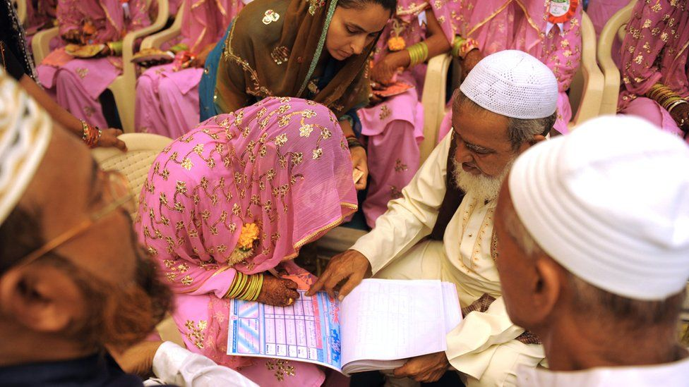 woman signing the marriage registry at a mass Muslim wedding in Gujarat in 2015