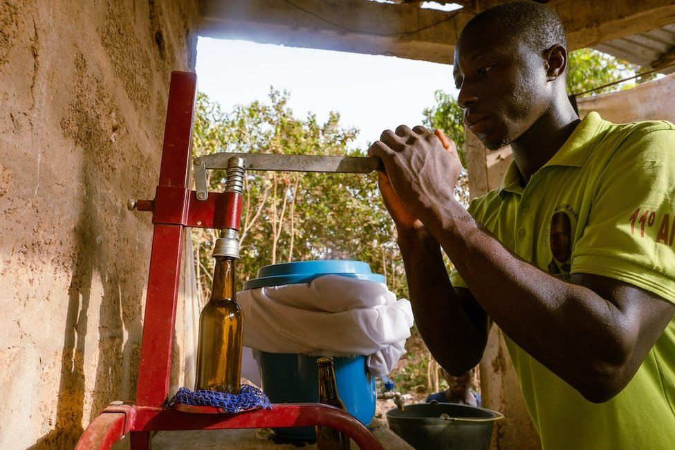 On Kumus Da Silva's local small scale cashew juice creation site, after workers sift out cashew juice they bottle and stamp the bottles before it is warmed in metal barrels to prevent fermentation.