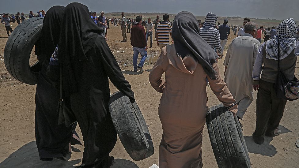Palestinian female protesters carry tires during clashes after protests near the border with Israel in the east of Jabaliya in the northern Gaza Strip
