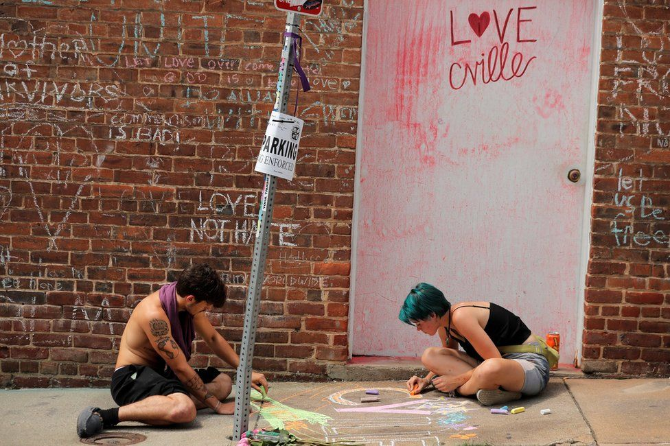 "People draw on a sidewalk near a memorial to Heather Heyer ahead of the one year anniversary of the 2017 Charlottesville ""Unite the Right"" protests in Charlottesville, Virginia"