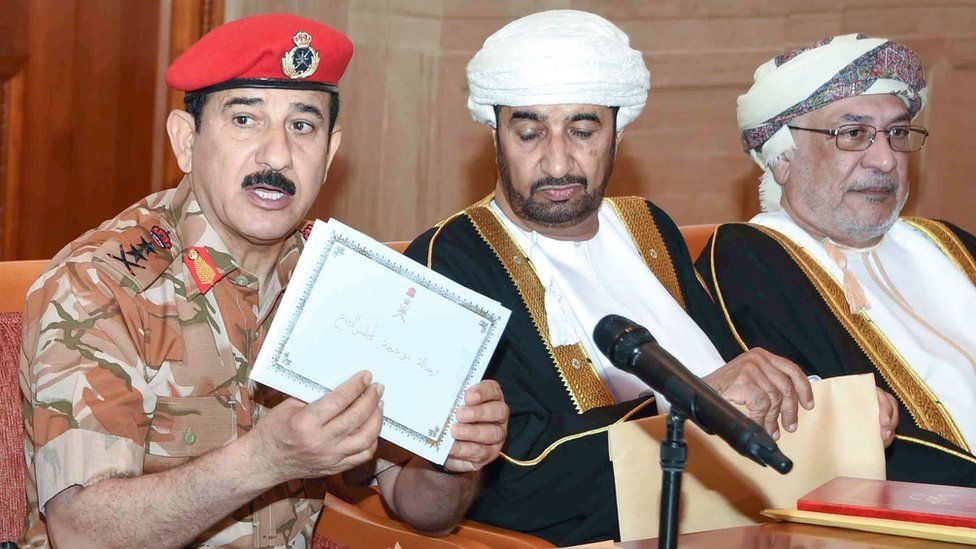 General Sultan bin Mohammed al Nomani (L) shows a letter from the envelope which contains the will of the late Omani leader Sultan Qaboos in the capital Muscat,