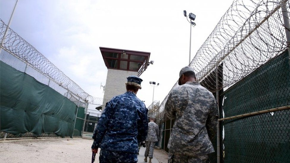 A US Navy sailor (left) walks with soldiers in Joint Task Force Guantanamo's Camp VI in Guantanamo Bay. Photo: March 2016