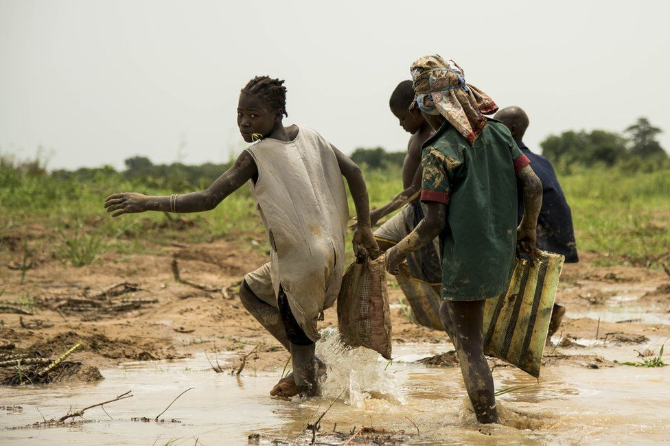 """In this photograph taken on August 15, 2017, children play in the waters of the River Chari in the Chadian capital of N""""Djamena, close to the border with Cameroon."""
