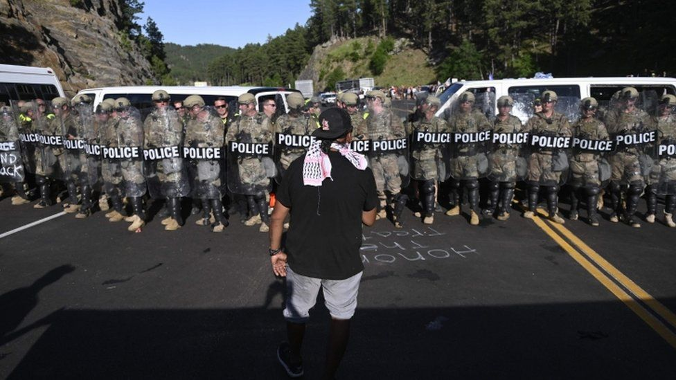 A man faces a row of police as activists and members of different tribes from the region block the road to Mount Rushmore National Monument in Keystone, South Dakota