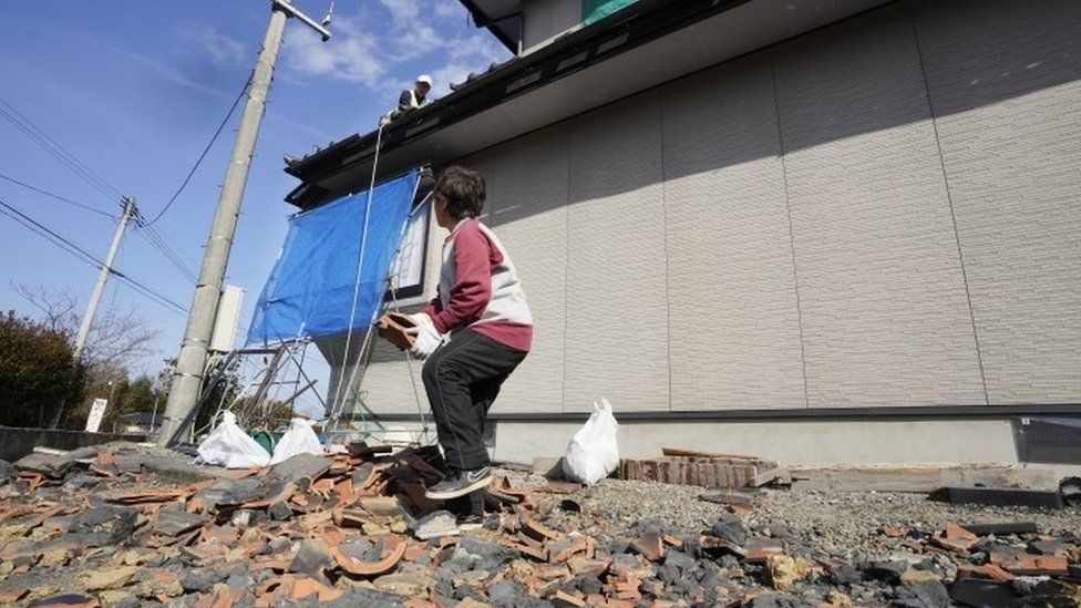 Residents collect belongings after an earthquake in Japan