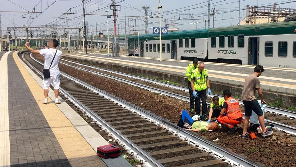 Man takes selfie next to injured person on train tracks