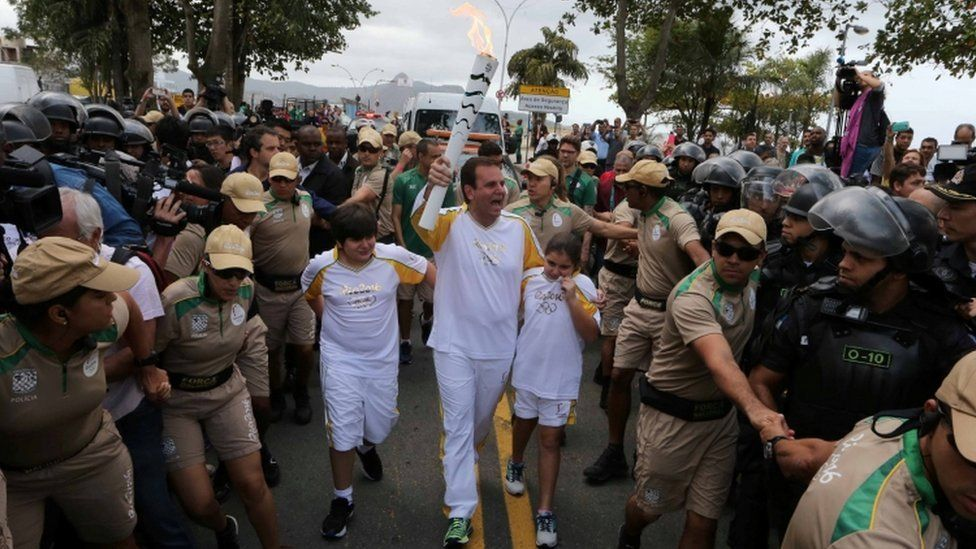 Mayor Eduardo Paes (C) carries the Olympic torch just after it was transported across Guanabara Bay from Niteroi to Rio de Janeiro three days before the official start of the Rio 2016 Olympic Games,