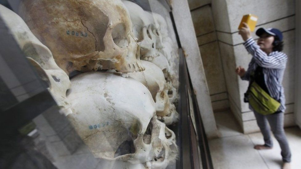 A tourist photographs a collection of skulls of victims who died during the Khmer Rouge regime, on display at the Choeung Ek Genocidal Centre on the outskirts of Phnom Penh on 6 August 2014