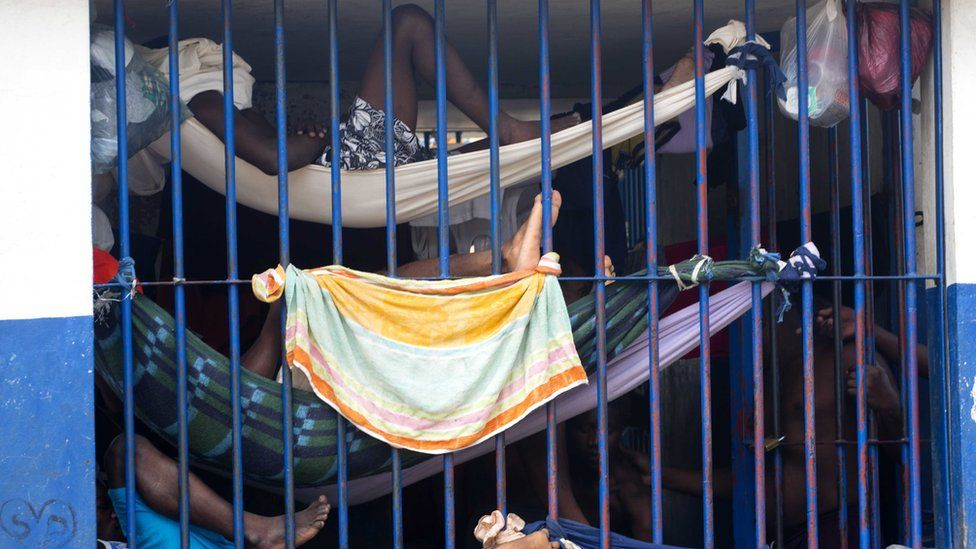 Prisoners rest in makeshift hammocks inside the National Penitentiary in downtown Port-au-Prince