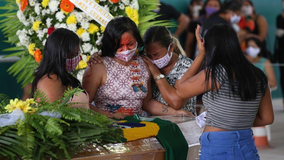 Indigenous from the Parque das Tribos community mourn besides the coffin of an indigenous leader