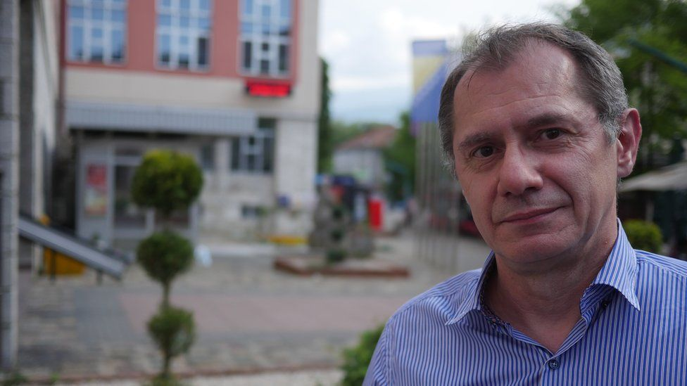 Davor Supa is pictured in a portrait, with the out-of-focus city streets stretching out behind him