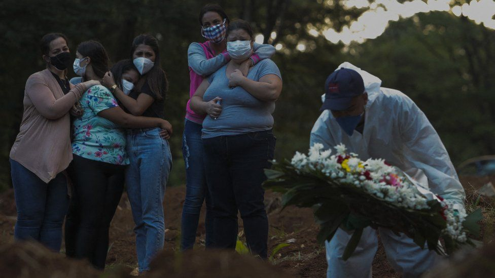 Relatives of a victim of the novel coronavirus disease Covid-19 mourn as their loved one is buried at the Vila Formosa cemetery in Sao Paulo