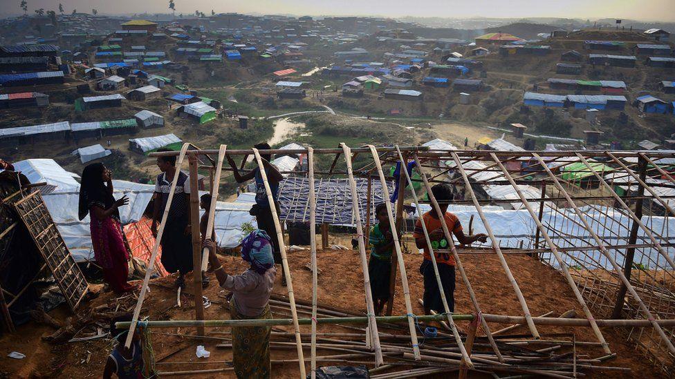 Rohingya refugee family rebuild a makeshift shelter at Balukhali refugee camp in the Bangladeshi district of Ukhia on November 22, 2017