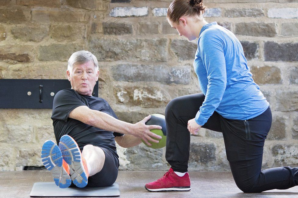 Senior man exercising with personal trainer