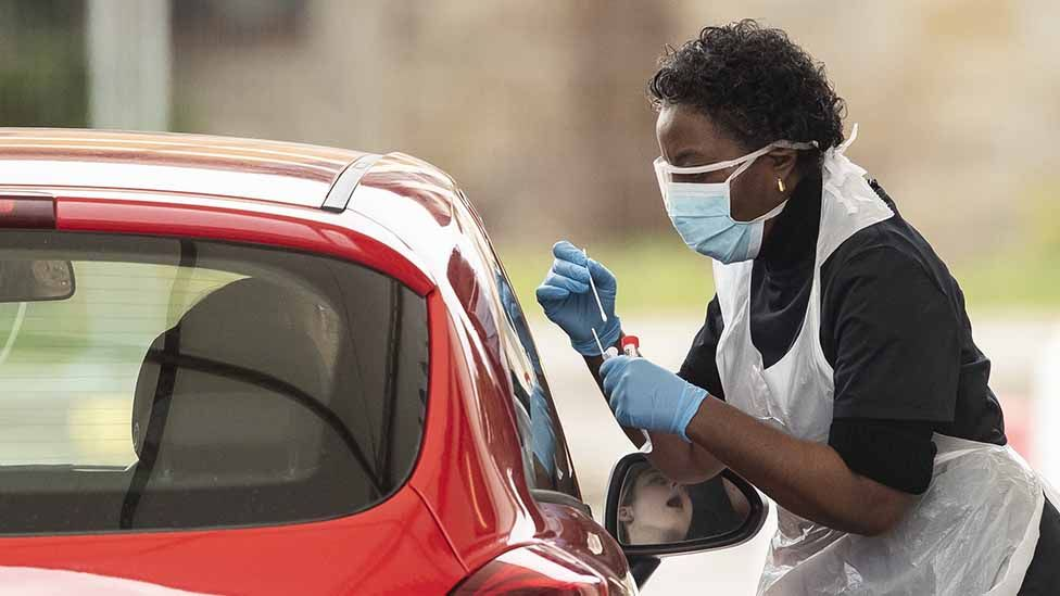 A nurse takes a swab at a Covid-19 Drive-Through testing station for NHS staff on March 30, 2020 in Chessington