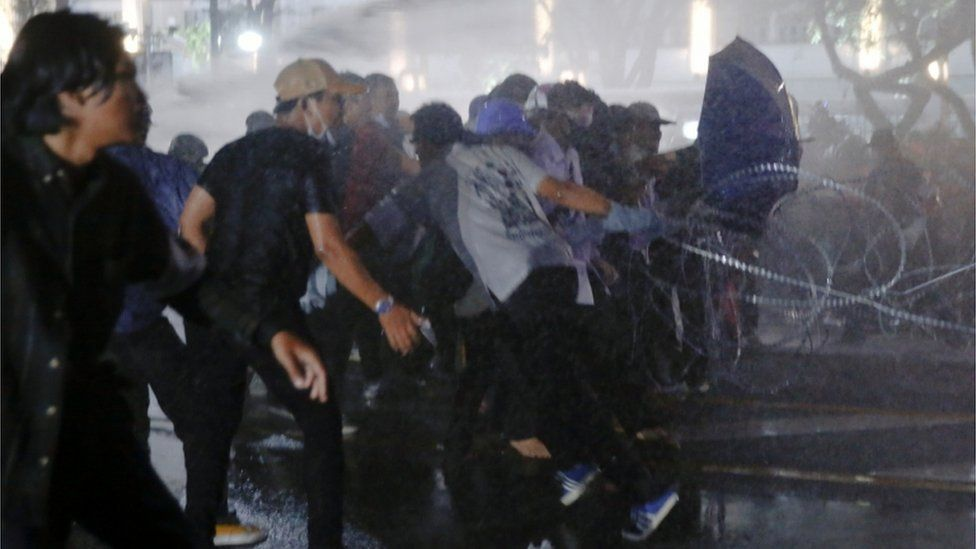 Protesters run as police use water cannon against them in Bangkok