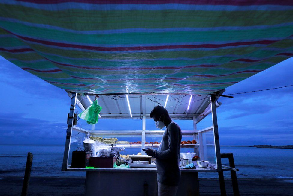 A street vendor wearing a face mask uses his mobile phone while waiting for customers at his food stall near a beach in Colombo, Sri Lanka, 12 January 2021.