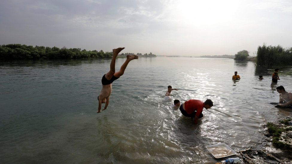 An Iraqi boy dives into the Tigris river in Mosul