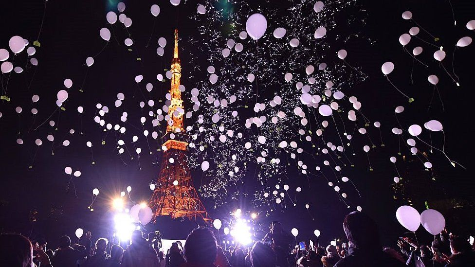 People celebrating New Year at Tokyo Tower on 1 January 2016, showing balloons and the tower lit up.