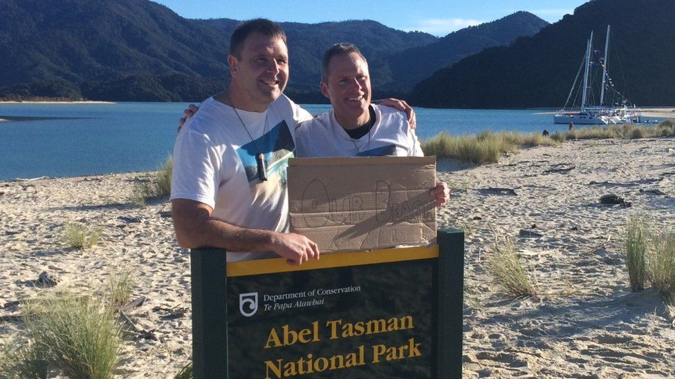 Two campaigners hold a sign saying 'Our beach' as they stand on a beach in New Zealand - 10 July 2016