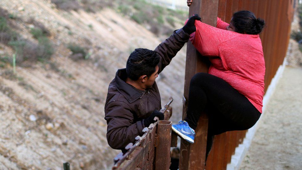 Migrants from Honduras, part of a caravan of thousands from Central America trying to reach the United States, jump a border fence to cross illegally from Mexico into the US, in Tijuana, Mexico, 27 December 2018