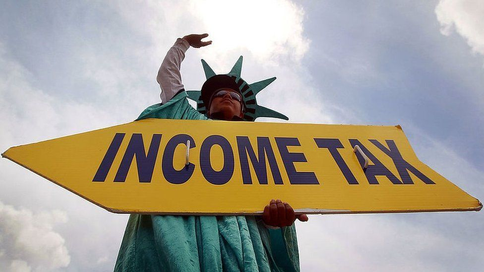 Man holding sign says 'Income tax' dressed as Statue of Liberty