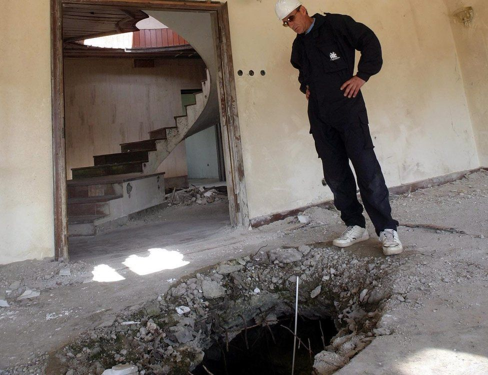 Former Serbia and Montenegro army officer Martin Martinovic stands between two holes in roof and floor of Chinese ambassy in Belgrade, Friday, 18June 2004.