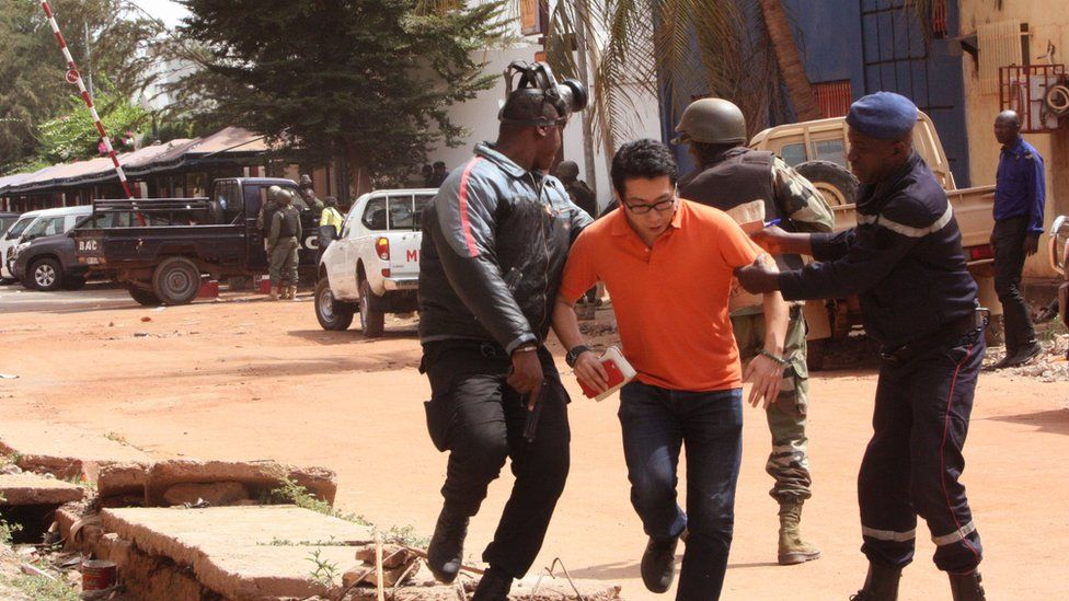Mali troops assist a hostage, centre, to leave the scene of the hotel