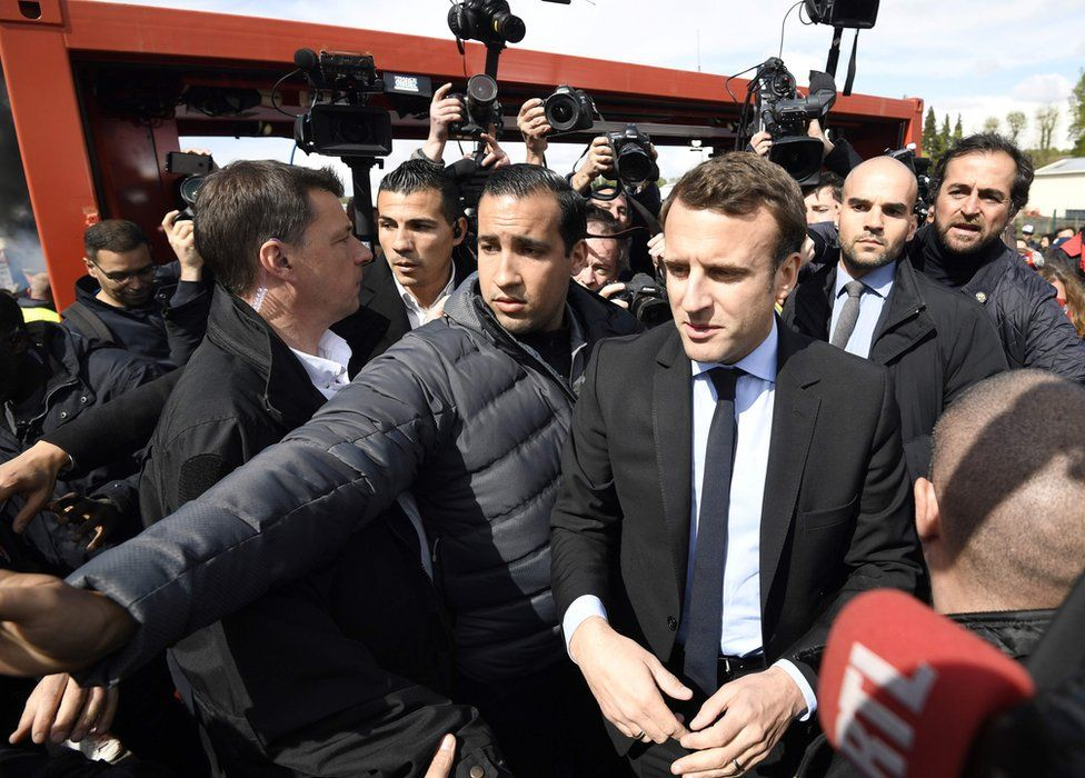Emmanuel Macron (L) is surrounded by journalists as he talks to Whirlpool employees in front of the company plant in Amiens, France, 26 April