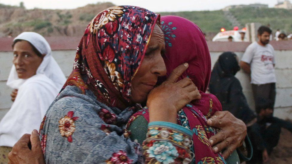Women mourn the death of their relatives who were killed