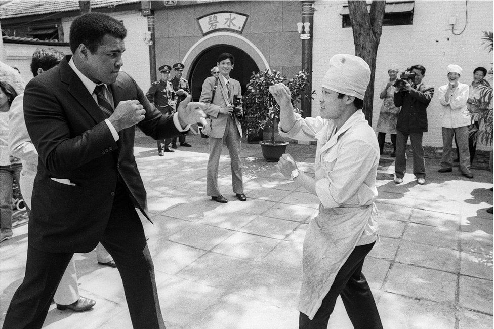 Muhammad Ali sparring with a man in the street