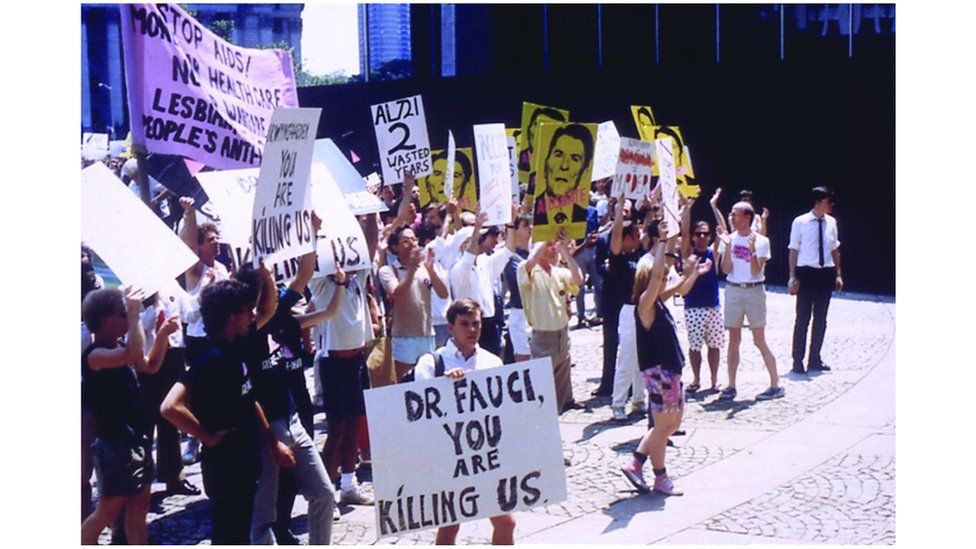 """Aids activist holds a sign reading: """"Dr Fauci you are killing us"""""""