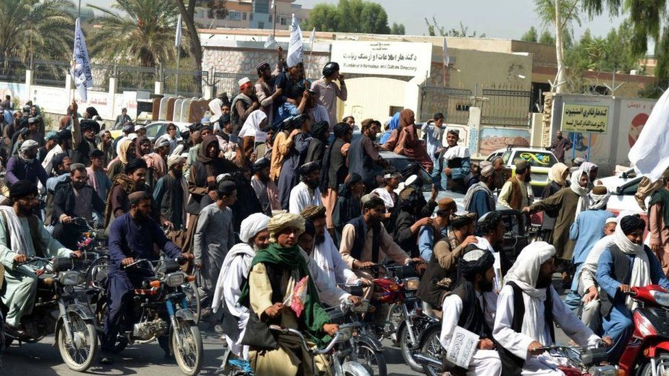Taliban supporters celebrate along a street in Kandahar on August 31, 2021