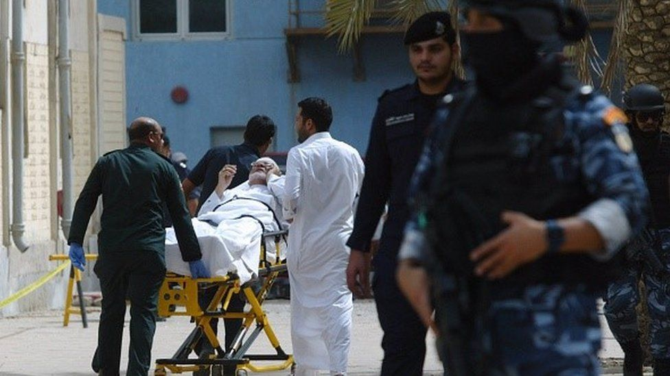 Kuwaiti emergency personnel pull a man on stretchers past security forces outside the Shiite Al-Imam al-Sadeq mosque after it was targeted by a suicide bombing during Friday prayers on June 26, 2015, in Kuwait City. T