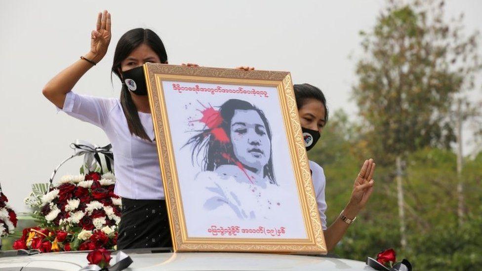 Myanmar women hold up a portrait of slain protester Mya Thwe Thwe Khaing