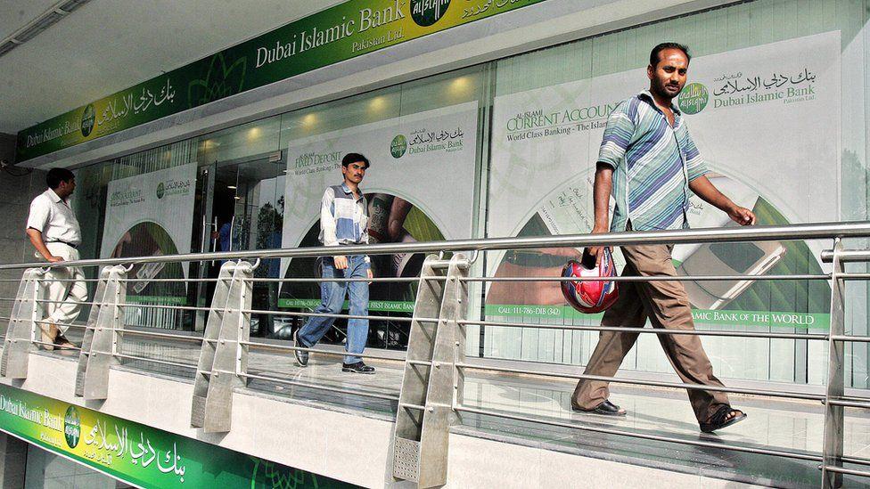 Pakistani men walk by a branch of the Dubai Islamic Bank in Islamabad, 23 May 2006