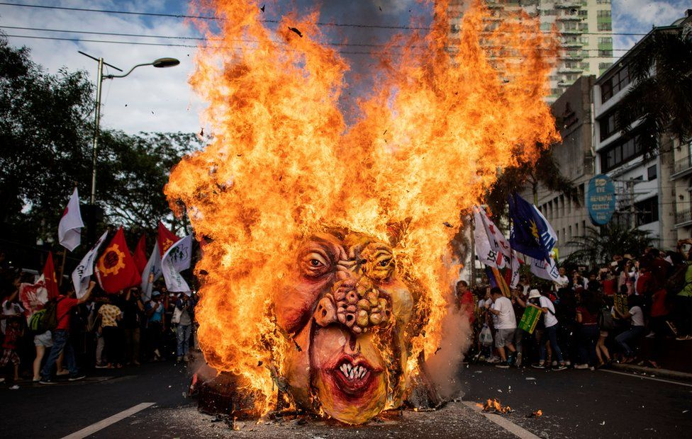 A large effigy is burned in the street