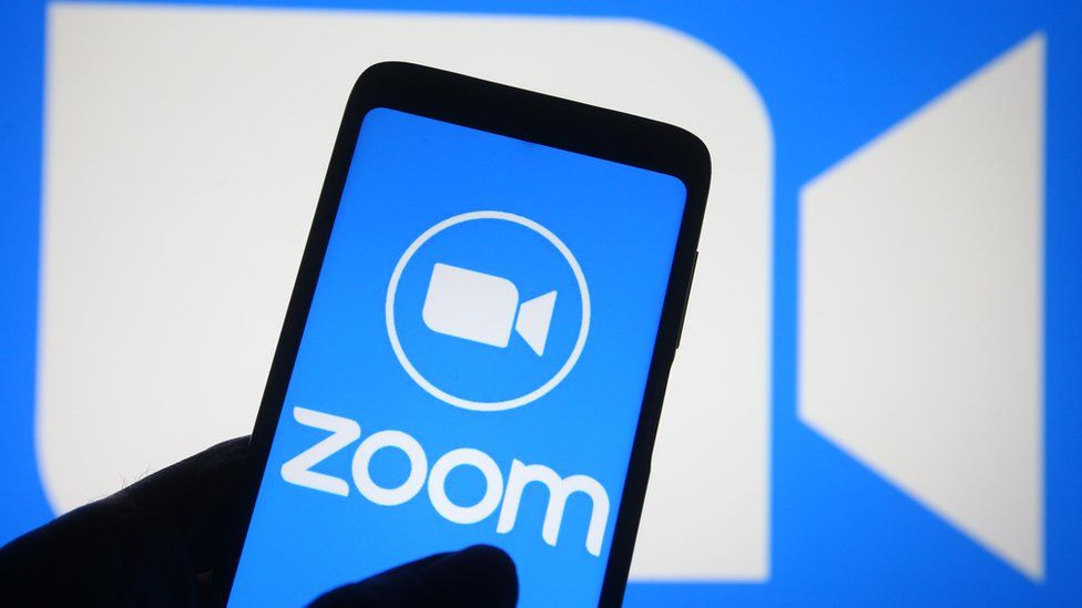 The Zoom video conferencing app is shown on a phone and a screen