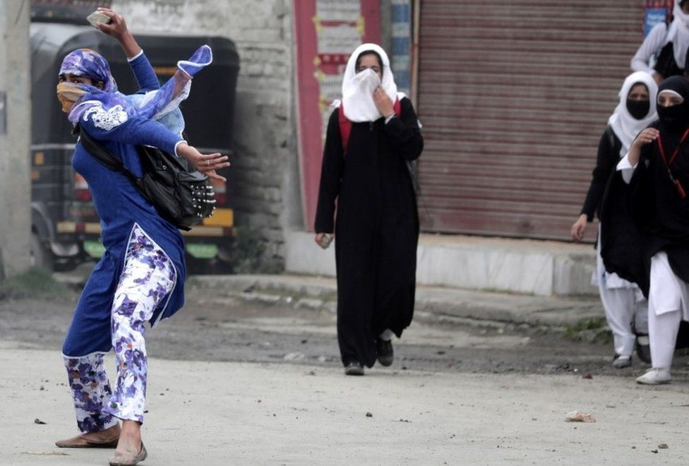 A Kashmiri female student throws a rock on police during clashes in Srinagar, the summer capital of Indian Kashmir, 24 April 2016