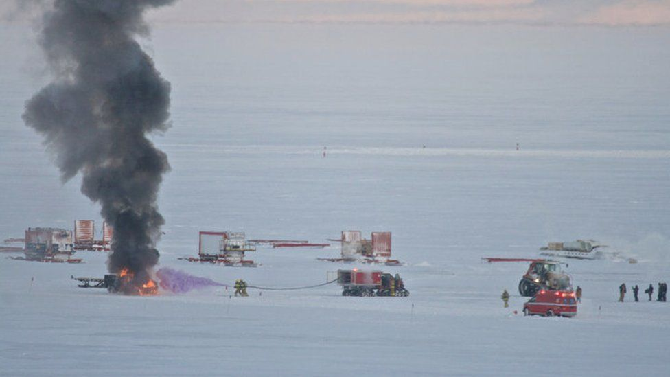 Smoke rises from a vehicle fire on an ice field. Fire-fighters spray a purple chemical on it