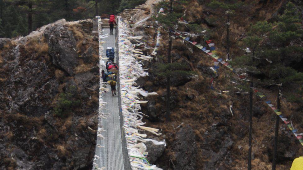 The team climb a wire suspension bridge