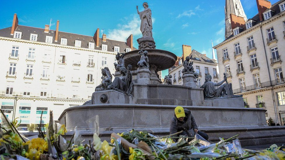 A FC Nantes football club supporter places flowers in the main square of the city of Nantes
