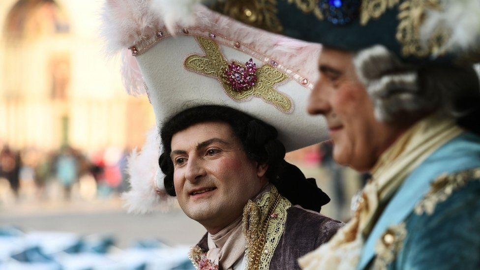 Two men in costumes stand in Venice