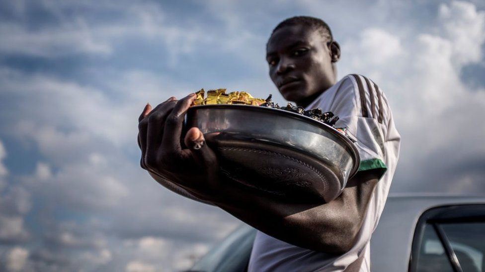 A street vendor carries a tray of his merchandise at a busy intersection in Yaounde, on October 1, 2018.