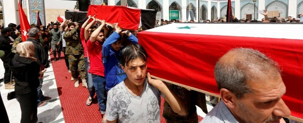 Mourners with coffins in Damascus