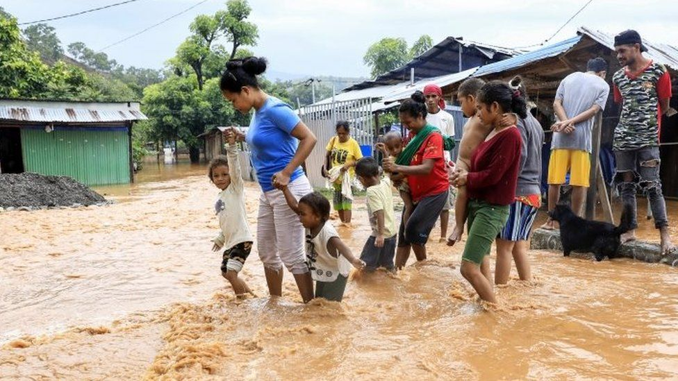 Residents wade through flood water in Dili, East Timor