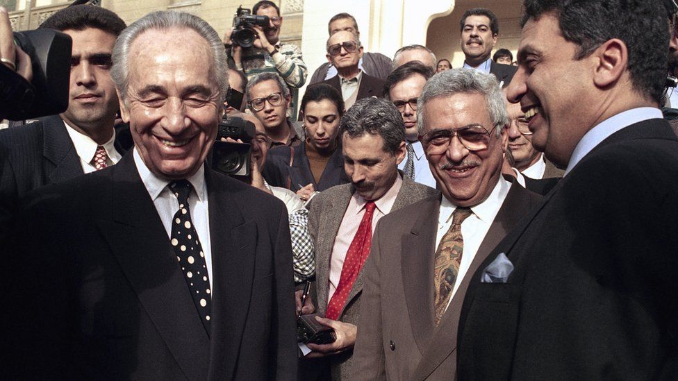In this Wednesday, Dec. 29, 1993, file photo, Israeli Foreign Minister Shimon Peres is all smiles along with PLO negotiator Mahmoud Abbas and Egyptian Foreign Minister Amr Moussa